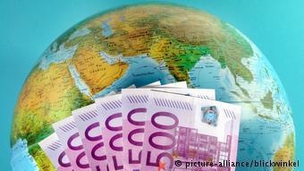 Пятисотевровые банкноты на фоне глобуса